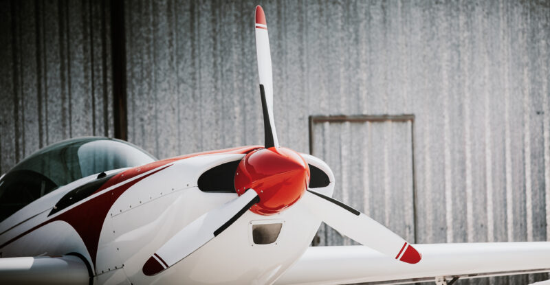 Close up of white and red small aircraft out of the hangar.