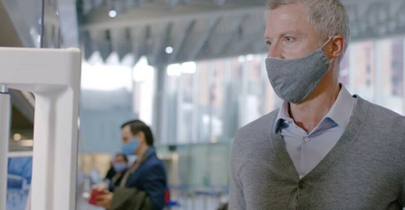a man with a mask on in the airport. A woman is seen with a mask on in the distance.