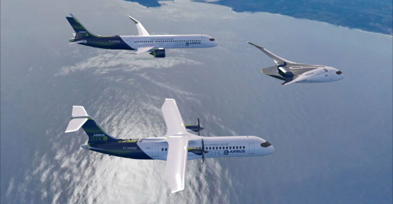 Three Airbus aircraft in flight over a large body of water. zero-emission is the goal.