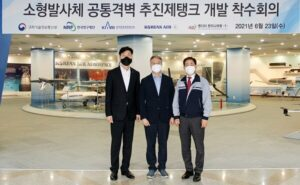 3 men with masks on posing for a photo