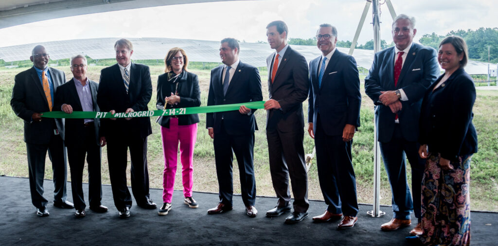 Group of men and women at PIT cutting a ribbon to celebrate the new Microgrid