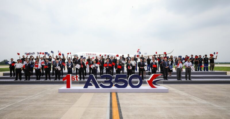 A large group of people standing behind a A350 sign with the aircraft in the behind them.