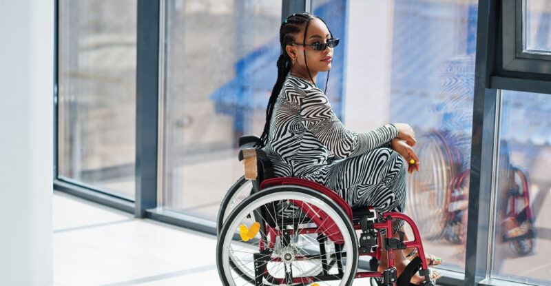 Young disabled African American woman in wheelchair at home.