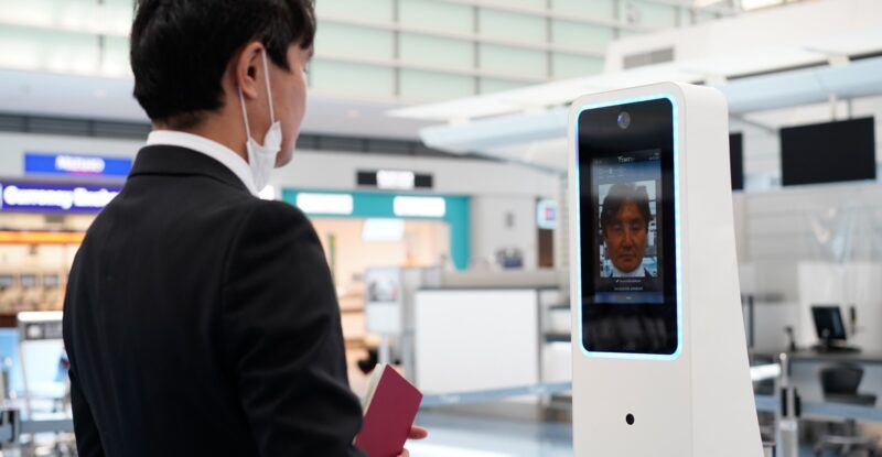 Asian man with a lowered mask using a biometrics kiosk at Tokyo Haneda Airport Image provided by Collins Aerospace