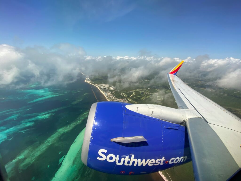 Southwest airlines wing tip from the aircraft window. Looking over the ocean.