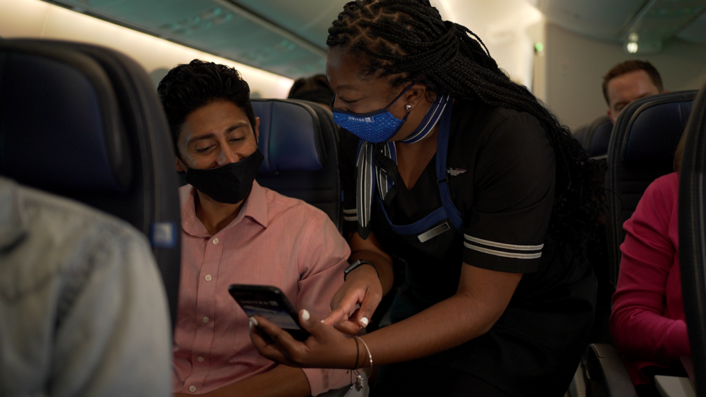 United flight attendant showing a passenger how to use pre-order for snacks.