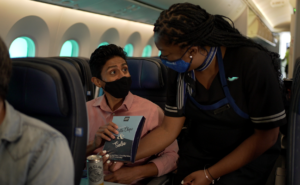 A female flight attendant in a mask hands a male passenger a bag of chips