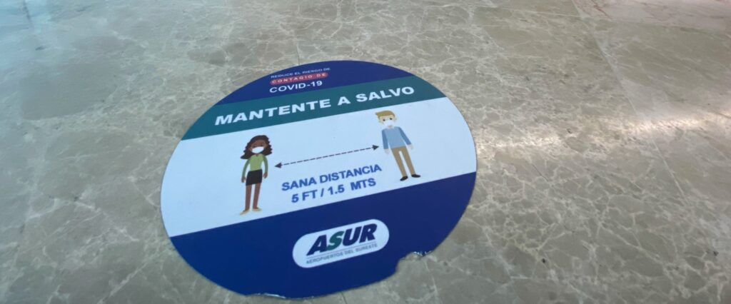 A sign on the floor at CUN, urging passengers to socially distance