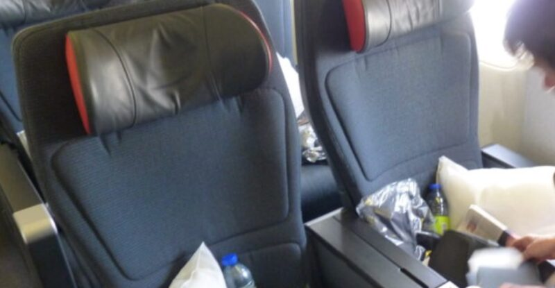 Two premium economy seats with pillows and water bottles waiting for the passengers