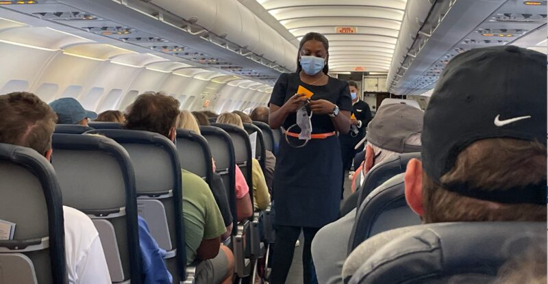 A masked flight attendant does the safety demonstration on board