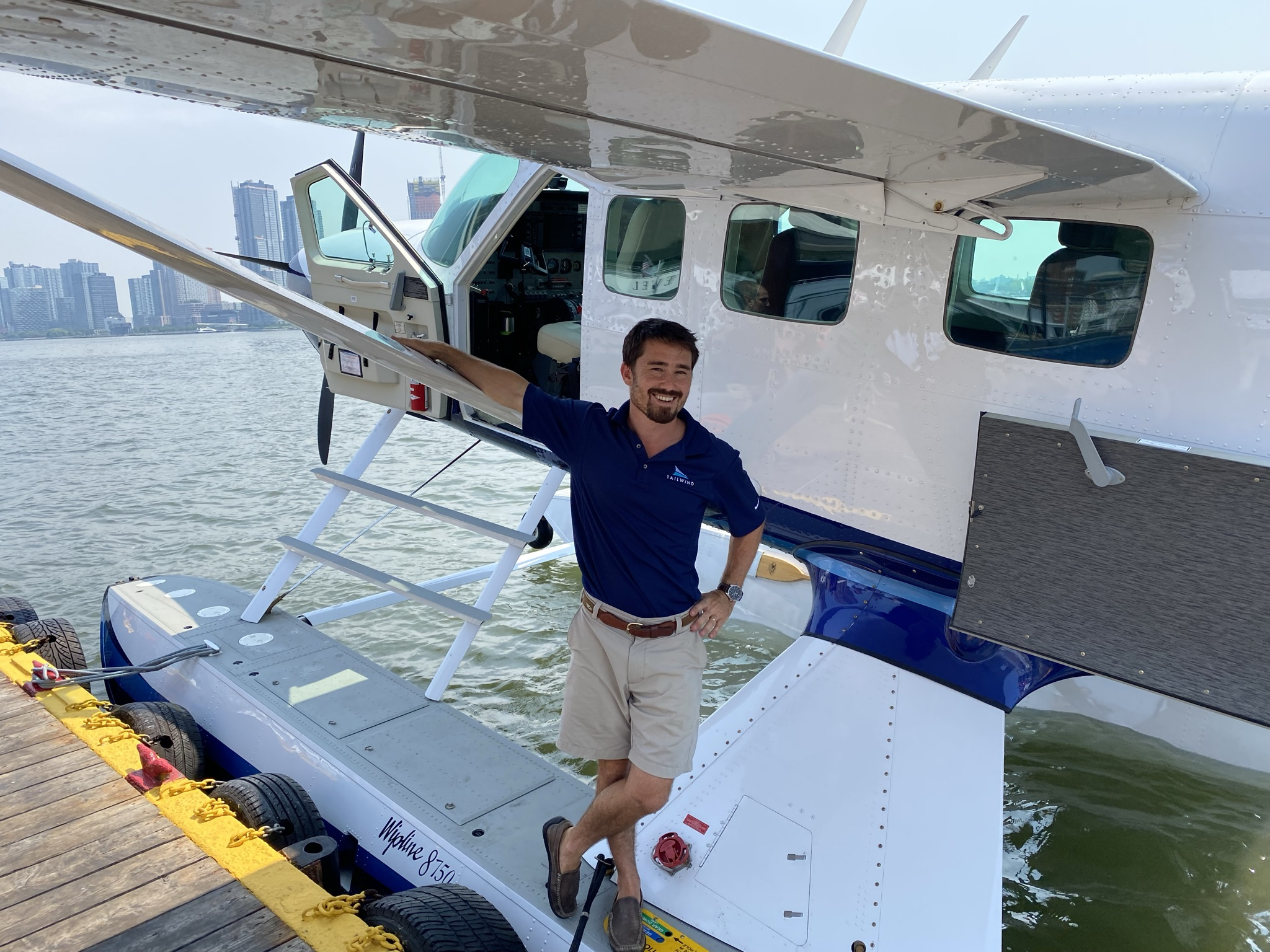 Tailwind seaplane at the dock prepping for flight, with a pilot standing in front of the aircraft, smiling