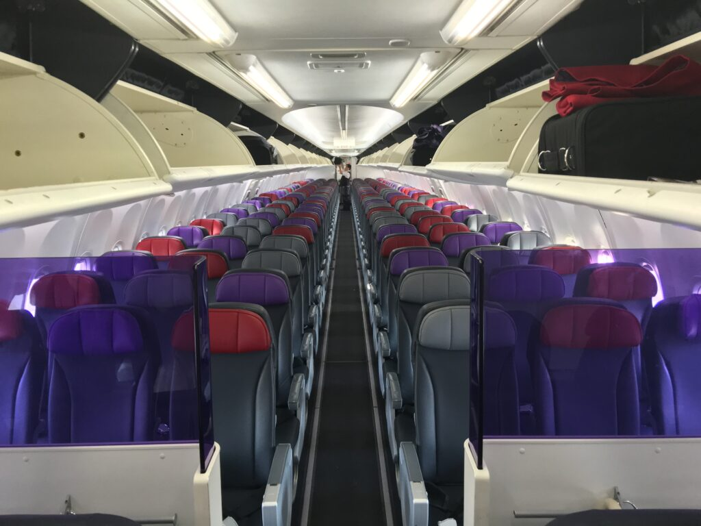 Rows of seats with two purple half-tinted, mini dividers in view