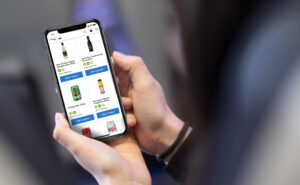 Person holding up a mobile device that is on the British Airways food and beverage ordering page.