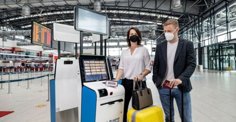 Couple at an airport wearing masks and using the SITA smart path