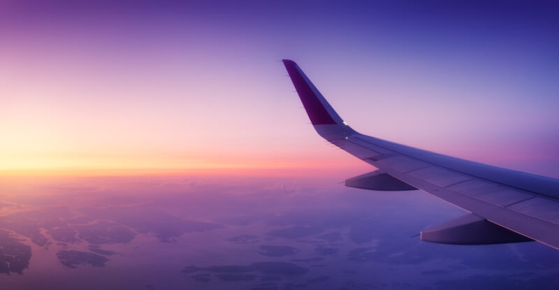 A wing of an aircraft flying through a glorious sky, with purple, orange and yellow in the scene