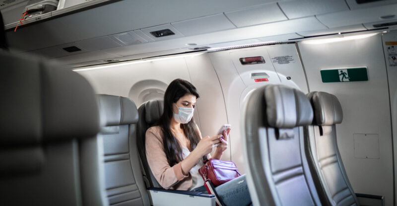 Young woman sitting using phone on the aircraft seat wearing face mask