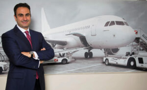Hassan El Houry, CEO pictured in front of a commercial aircraft at the gate.