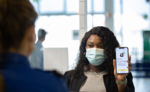IATA travel pass being shown to a check in agent by a passenger via a mobile device