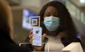 A woman wearing a mask is showing a crew member her IATA travel pass app on her mobile device.