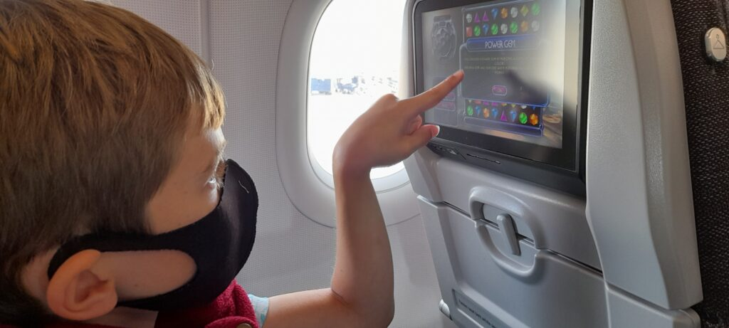 The author's child, wearing a black mask, uses the seatback IFE onboard an Aer Lingus A321neo