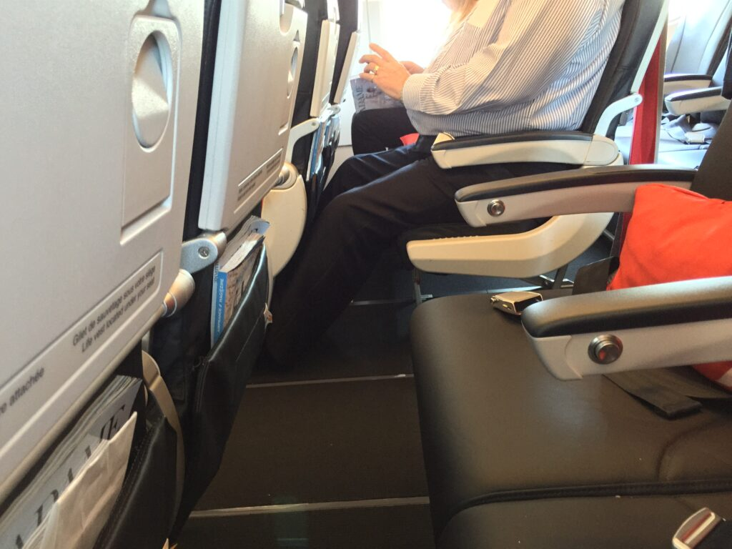 Waist level shot of people sitting on an aircraft with little room to move.