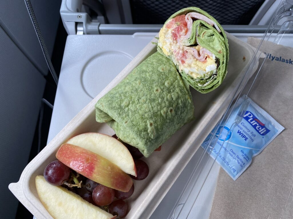 The egg and ham sandwich wrap is pictured on the tray table, with a Purell wipe sitting beside it