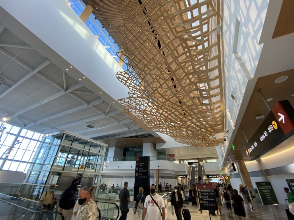 SeaTac's new terminal with many passengers in it. Light is streaming in from windows overhead and on the side of the building, and a unique wooden art installation is in view