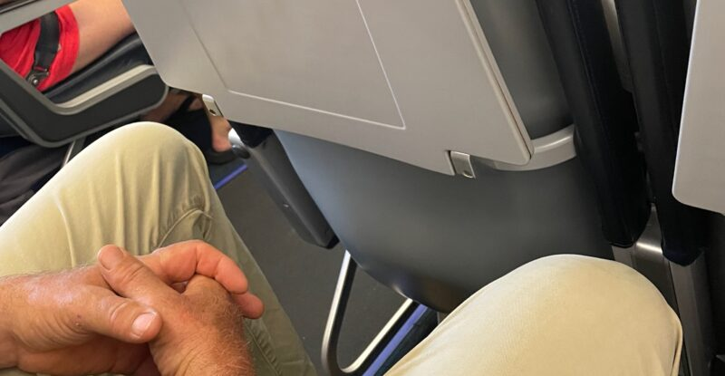 A man seated in an aircraft seat with hands folded. His legs are in view, and shown close to the seatback in front of him
