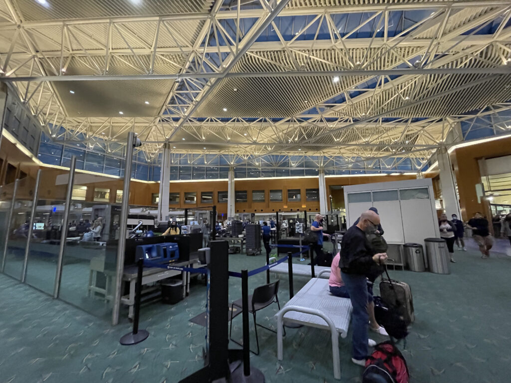 Portland Airport Security in a large temporary open space. Masked passengers are seen in different areas.
