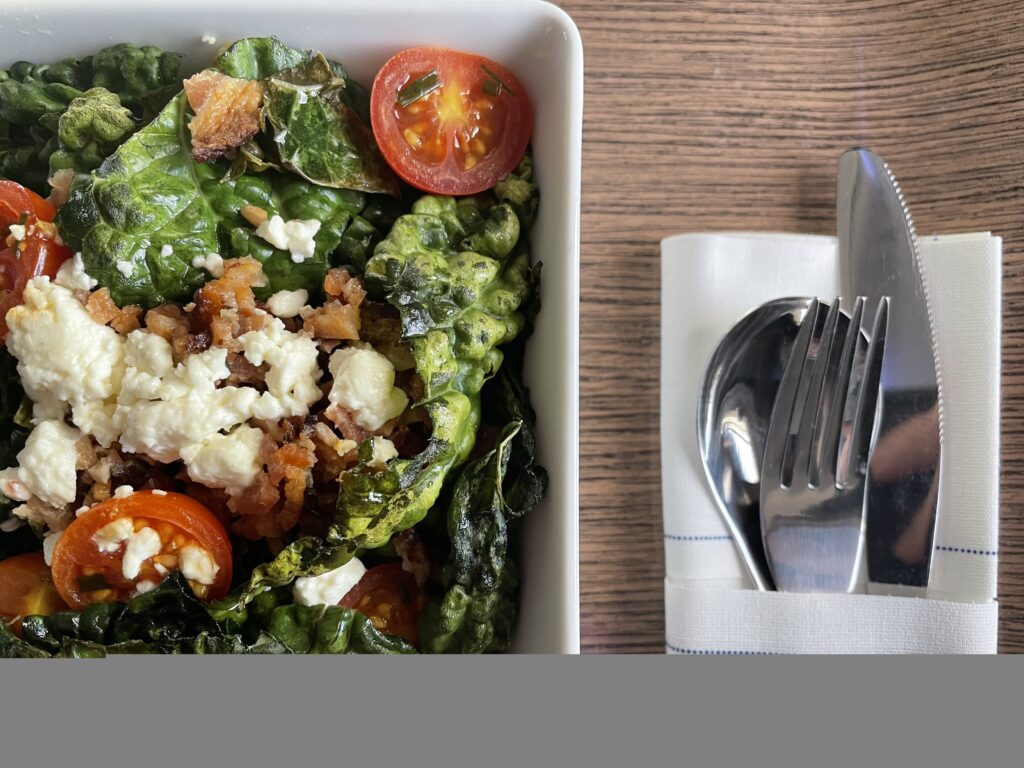 A beautifully dressed salad accompanied with silverware