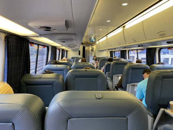 Interior of Acelra Amtrak train car. With grey seating. Some passengers are already seated.
