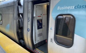 Amtrak Acela car with an open door for passengers to board. The car is listed as Business Class.