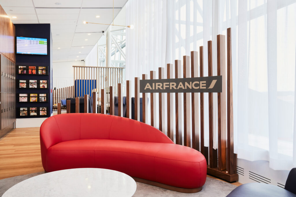 Air France lounge in Montreal Airport (YUL) with a large red couch in front of an Air France logo.