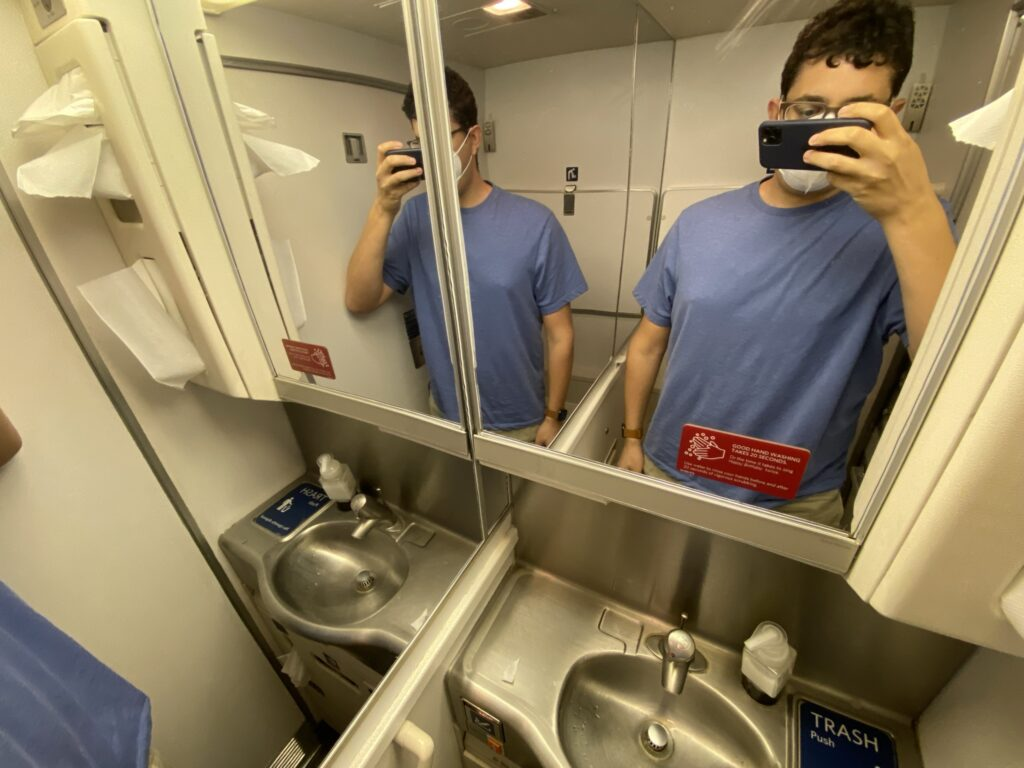 The author, Jason Rabinowitz, taking a mirror selfie in the aircraft lavatory.