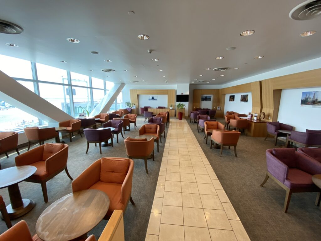 JFK Airport terminal 4 Air India Lounge with brown and purple chairs, and lots of light from the window