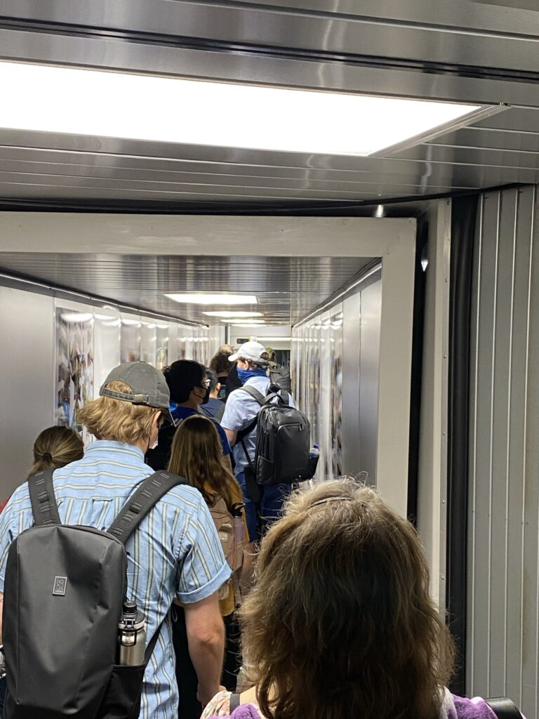 People in the jetbridge, readying to board the Delta Aircraft.