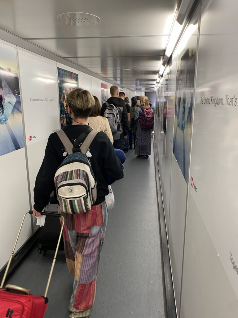 passengers lining up on the jet bridge for boarding.