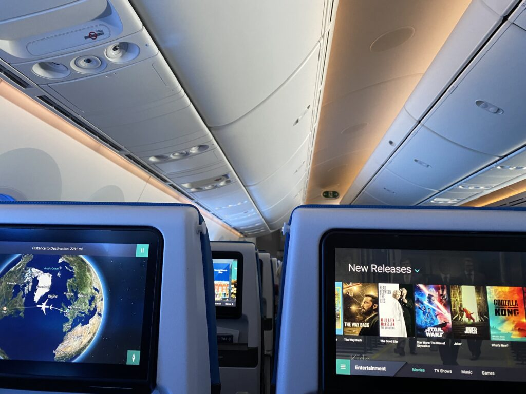 WestJet Economy class embedded IFE Screens. One showing movie selection and the other showing Flightpath 3D Moving map.