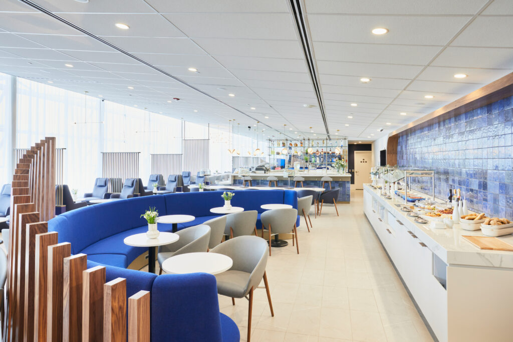 Air France lounge in Montreal. The buffet is in view, as well as blue chairs and a large semi-circle blue sofa to support multiple seating options