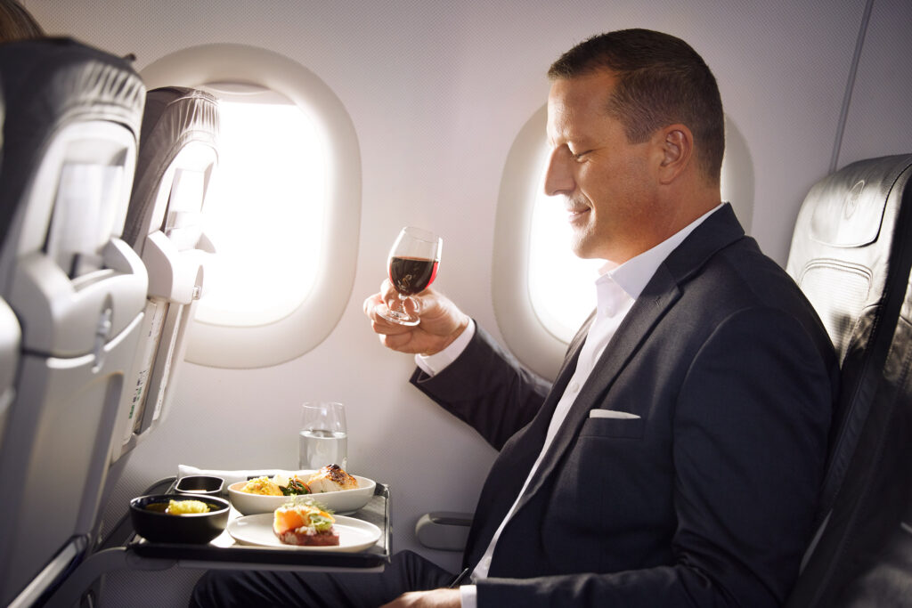 Business Class passenger enjoying an inflight meal with a glass of wine.