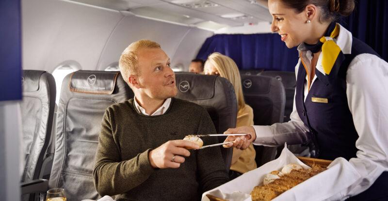 Flight attendant serving a piece of bread to a Business Class passenger.