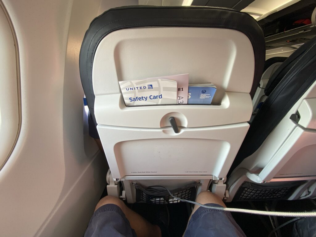 United Airlines A320 Economy class seat. View of a man's knees and the seatback in front of him. There is no device holder, only a high literature pocket and the tray table