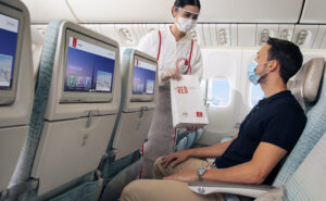 Emirates female flight attendant handing a male passenger a bag purchased from duty free. Both flight attendant and passenger are wearing masks.