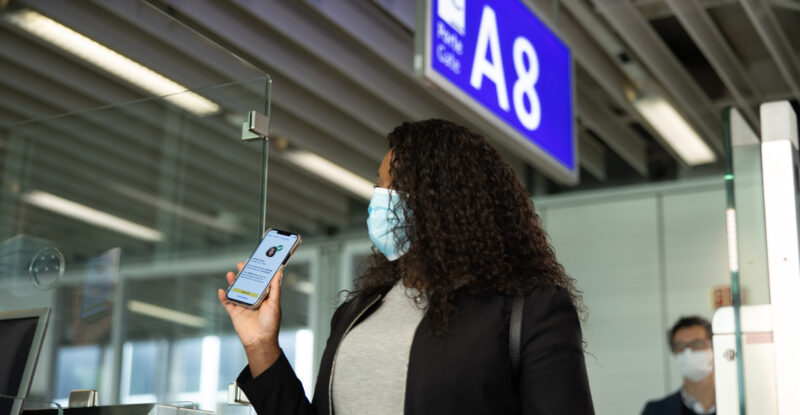 A woman shows the IATA Travel Pass to a boarding agent at the airport
