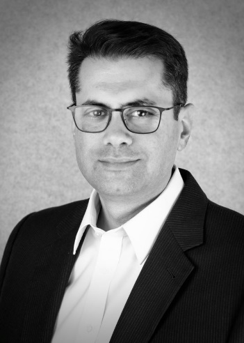 A black and white headshot of Anuvu CEO Josh Marks