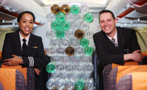 Two crew members in uniform on an aircraft next to a stack of water bottles.