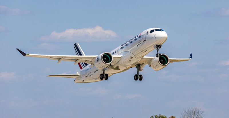Air France A220-300 taking off. There are trees and a clear blue sky in the background.
