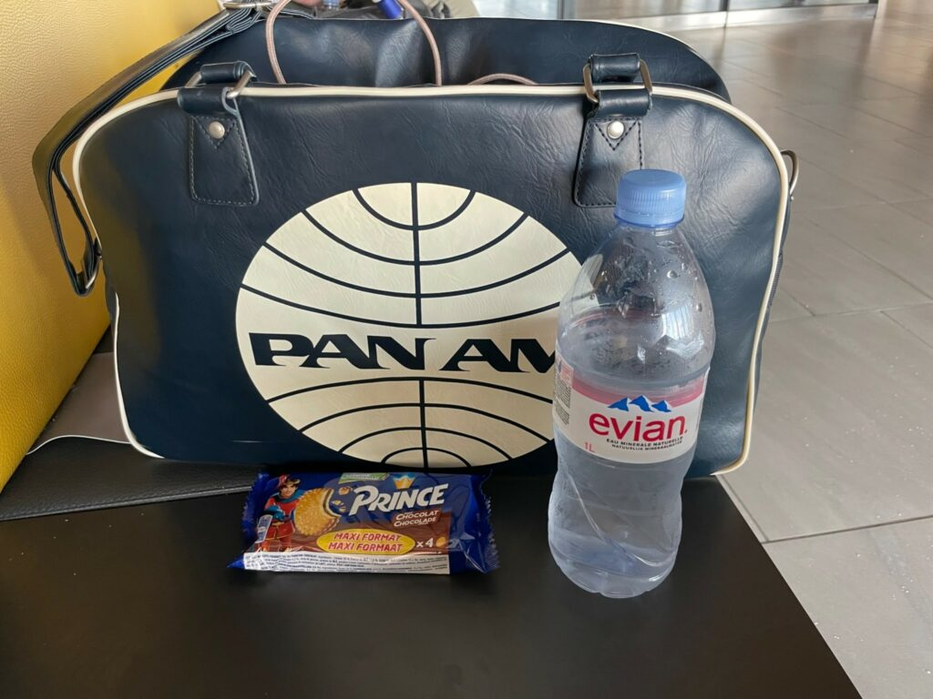 A Pan Am bag sits on a table with a bottle of water and a snack.