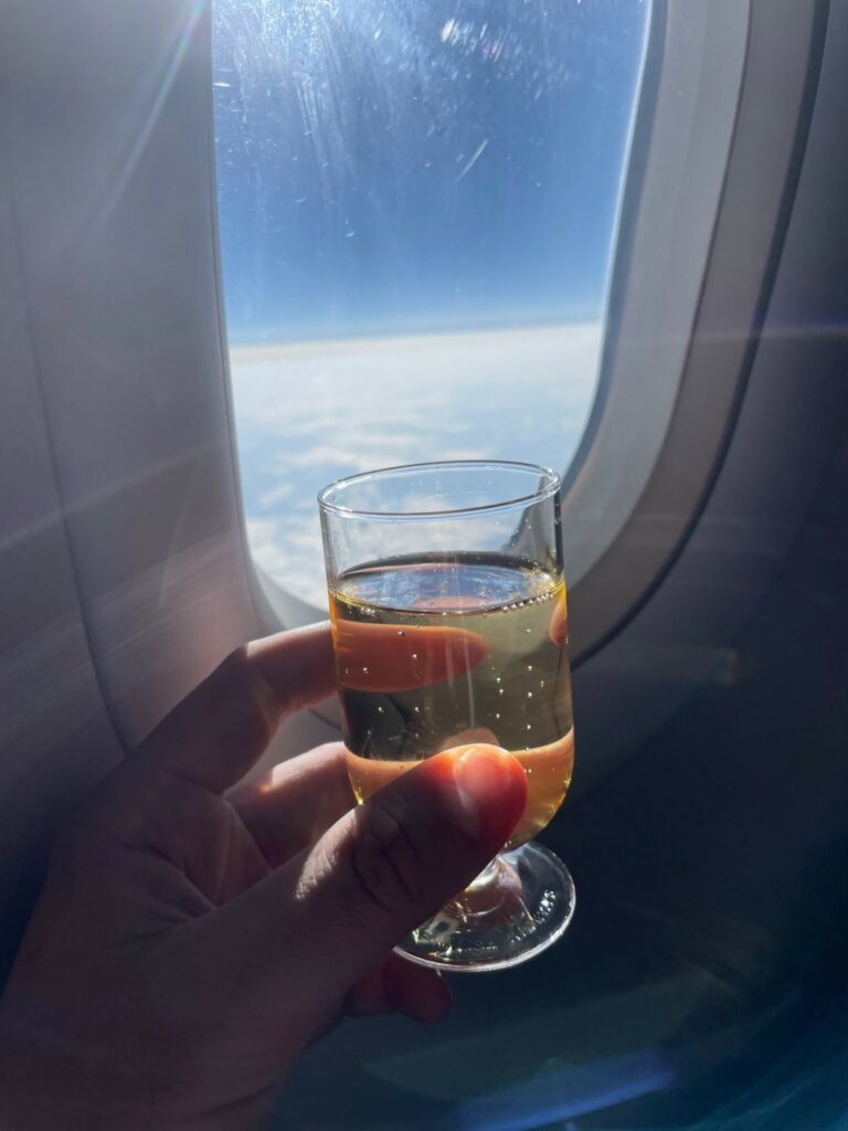 Hand holding a glass of champagne in front of an aircraft window on British Airways.