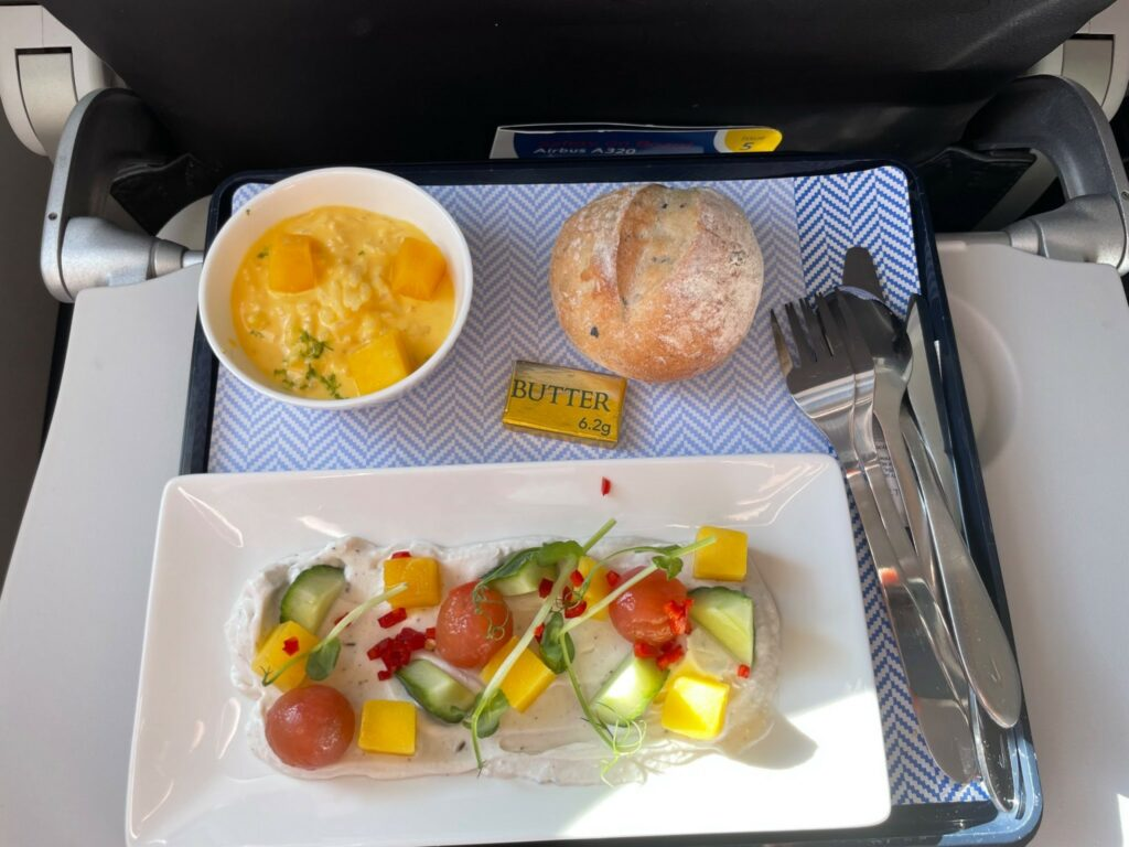A British Airways meal that was served inflight consisting of fruit, bread and more.